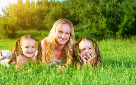 niños felices: madre de familia y niños hermanas gemelas felices en prado en el verano en una hierba verde Foto de archivo