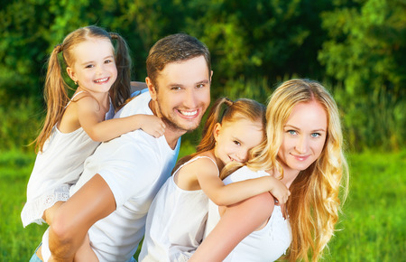 family in the park: happy family on the nature of the summer, mother, father and children twin sisters