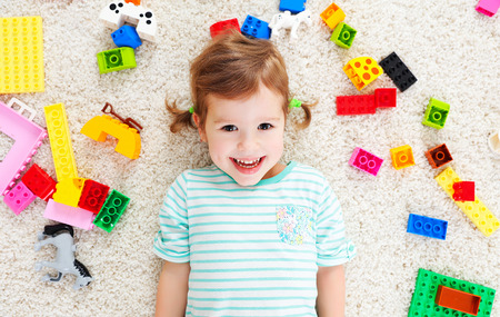 constructor: happy child girl laughing and playing with toys constructor Stock Photo