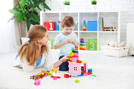 母と子の娘が一緒に遊ぶ、コンス トラクターからのビルド