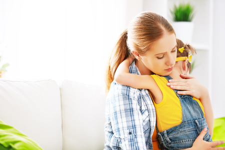 sad little girl: child girl daughter in an embrace his mother Stock Photo
