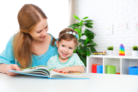mother and child reading a book together at home Stock Photo