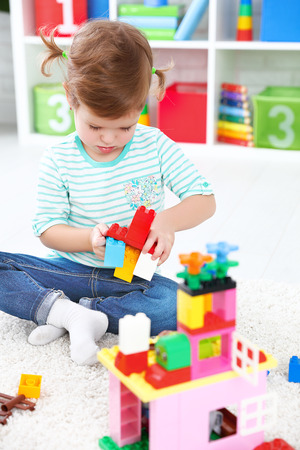 builds: Happy child girl playing with toys and builds constructor Stock Photo