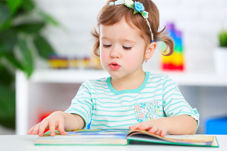 cute baby girl reading a book at home