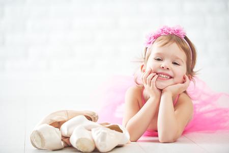 klein kind meisje droomt ervan om ballerina met ballet schoenen en pointe schoenen in een roze tutu rokje