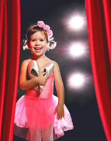 ballerina costume: little child girl ballerina ballet dancer on the stage in red side scenes