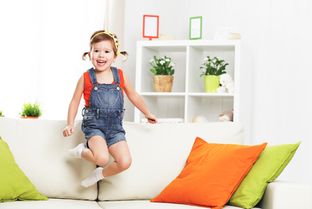 personas saltando: niña feliz niño jugando y saltando en el sofá de casa