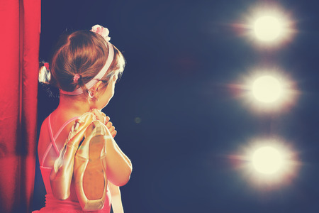 little child girl ballerina ballet dancer on the stage in red side scenes and looking in odeum Archivio Fotografico
