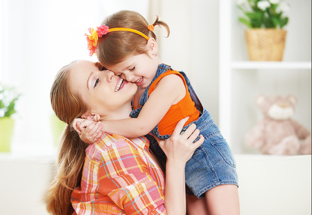 two women hugging: happy family mother and child girl daughter playing  laughing and hugging at home