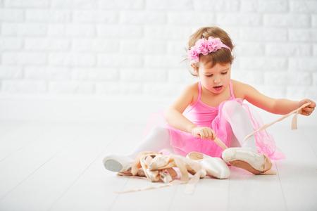 kleines Kind Mädchen träumt davon, Ballerina mit Ballett Schuhe und Spitzenschuhe in einem rosa Ballettröckchen-Rock