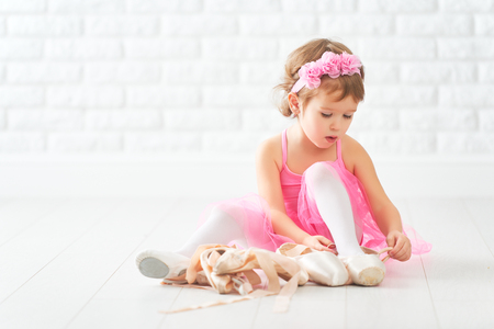 little child girl dreams of becoming ballerina with ballet shoes and pointe shoes in a pink tutu skirt