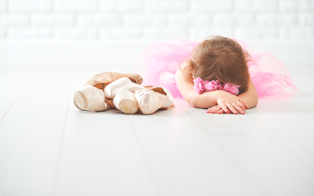 ballerina costume: little child girl  ballerina with ballet shoes and pointe shoes in a pink tutu skirt Stock Photo