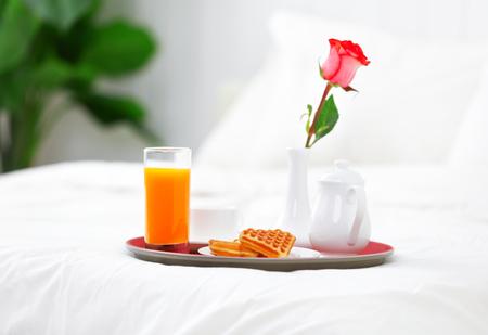 romántico desayuno en la cama y flor rosa Foto de archivo