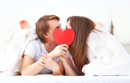 románc: koncepciója Valentin nap. szerető pár csók egy piros szív az ágyban