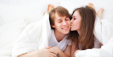 baiser amoureux: Heureux couple embrassant dans le lit furtivement de sous la couverture Banque d'images