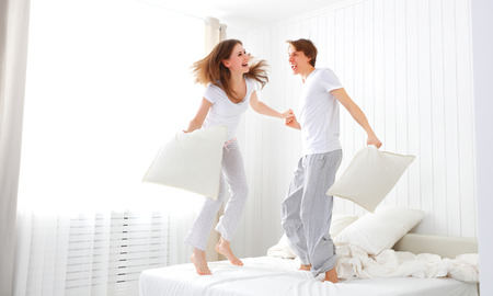 pajamas: Happy loving couple jumping and having fun in bed