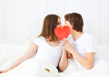 red bed: concept for Valentines Day. lover couple kissing with a red heart in bed Stock Photo