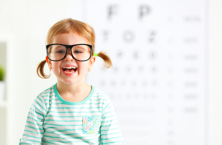 testing vision: concept vision testing. child  girl with eyeglasses at the doctor ophthalmologist