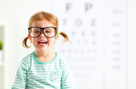 examen de la vista: concepto de prueba de visión. Chica niño con gafas en el oftalmólogo médico Foto de archivo