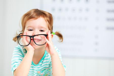 lentes de contacto: concepto de prueba de visión. Chica niño con gafas en el oftalmólogo médico Foto de archivo