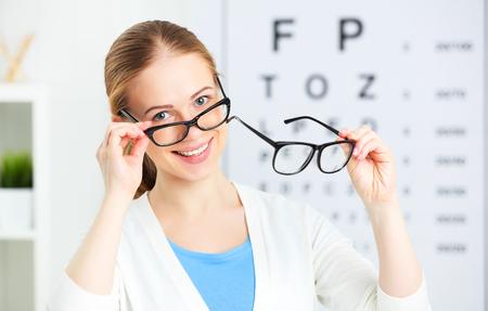 cheque vista. mujer elige los vidrios en el óptico médico oftalmólogo