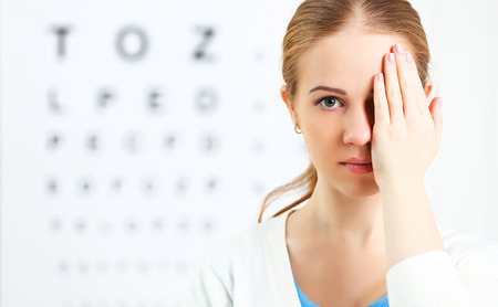 eyesight check. woman  at the doctor ophthalmologist optician 스톡 콘텐츠