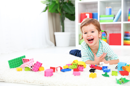 designer baby: happy child girl laughing and playing with toys constructor Stock Photo