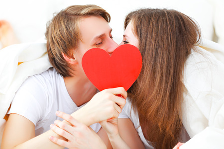 enamorados en la cama: concepto para el d�a de San Valent�n. pareja amante besando con un coraz�n rojo en la cama Foto de archivo