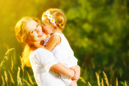 family with baby: Happy family on a summer meadow. little girl child baby daughter hugging and kissing mother