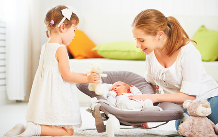nursing sister: happy family. mother and children newborn baby and big sister Stock Photo