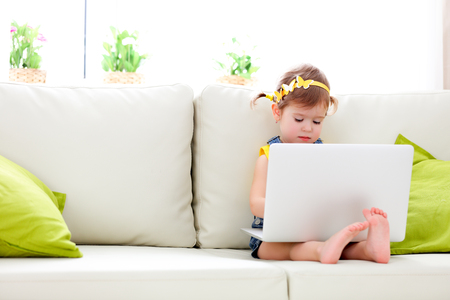 my home: child girl with a laptop at home on the couch