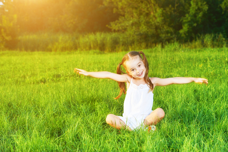 girl lying: happy child little girl spread his arms in a white dress lying on the grass Summer