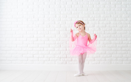 little child girl dreams of becoming  ballerina in a pink tutu skirt Imagens