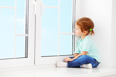 child girl dreams about windows Stock Photo