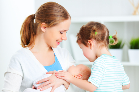 nursing sister: happy family. mother, newborn baby and big sister Stock Photo