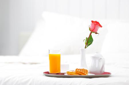 charolas: romántico desayuno en la cama y flor rosa Foto de archivo