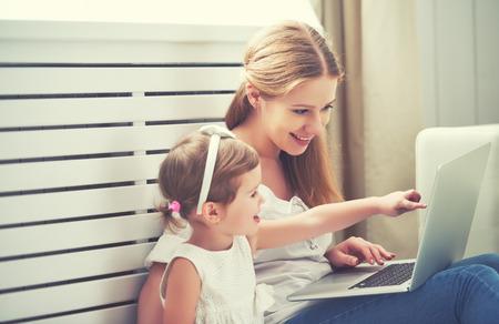 madre de familia y su hija hijo en casa con un ordenador portátil