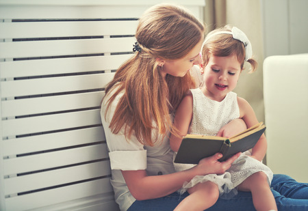 happy family mother child daughter little girl reading a book by the window