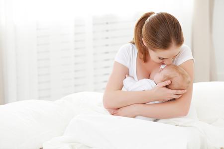 Bir mutlu bir aile yeni doğan bebek beyaz bir yatakta annesini kucaklamak Stok Fotoğraf
