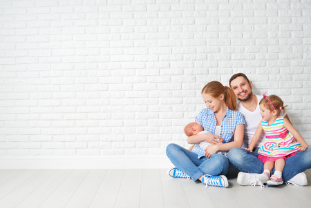 happy family father mother and children sitting on the floor in an empty brick wall