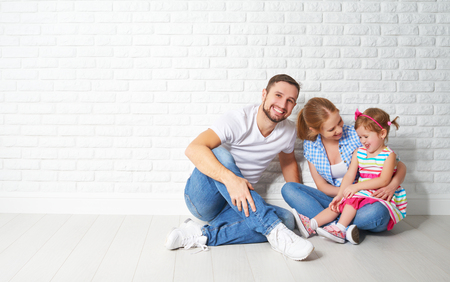 housing problems: concept of mortgage housing problems. family mother father child daughter at a blank white brick wall