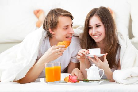 amantes en la cama: pareja de enamorados que desayunan en cama en el Día de San Valentín