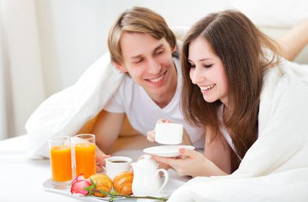 ロマンス: バレンタインの日にベッドで朝食を持っている愛するカップル