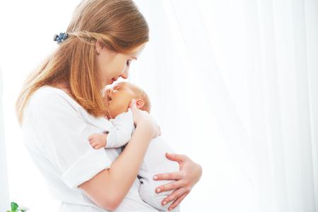 neugeborenen Babys in einer zärtlichen Umarmung der Mutter am Fenster