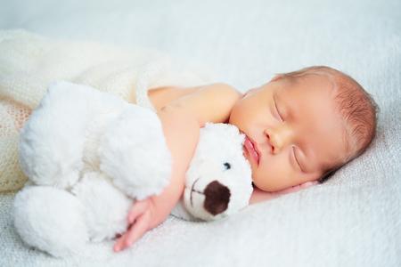 Leuke pasgeboren baby slaapt met een speeltje teddybeer wit