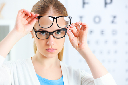 specs: eyesight check. woman choose glasses at the doctor ophthalmologist optician Stock Photo
