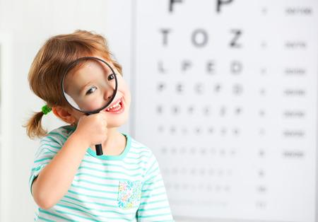 concepto de prueba de visión. Chica niño con una lupa en el oftalmólogo médico