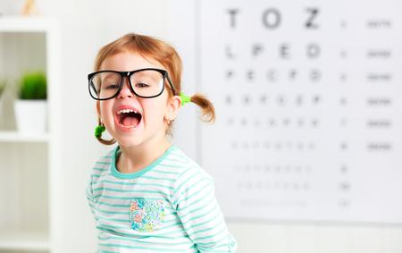 concepto de prueba de visión. Chica niño con gafas en el oftalmólogo médico Foto de archivo