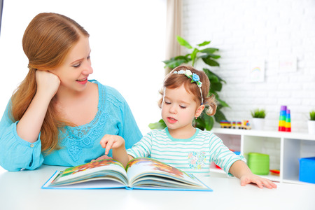 preschool kids: mother and child reading a book together at home Stock Photo