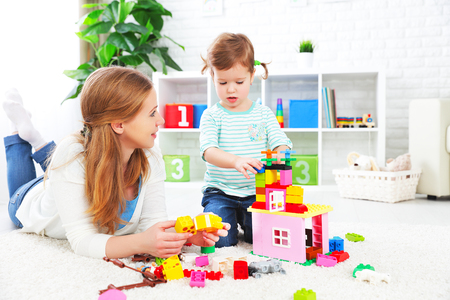 designer baby: Mother and child daughter playing together, build from the constructor